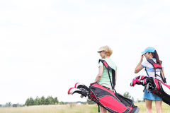 Rear view of women with golf club bags at course against clear sky Royalty Free Stock Photography