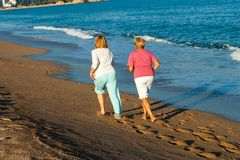 Rear view of women jogging on beach. Stock Photography