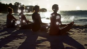 Rear view of women mediating on sand