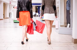 Rear view of women walking in mall with shopping bags Stock Photo