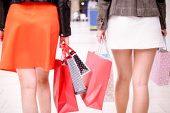 Rear view of women walking in mall with shopping bags stock image