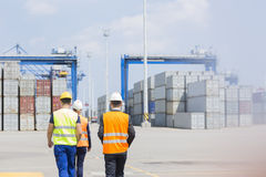 Rear view of workers walking in shipping yard Stock Images