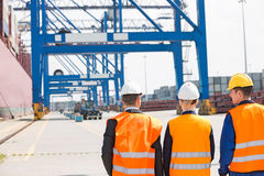 Rear view of workers walking in shipping yard Royalty Free Stock Photography