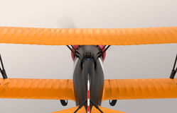 Rear view of yellow and black biplane flying in the sky Stock Image