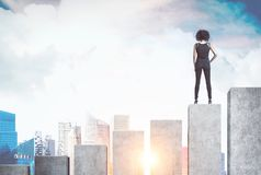 African American businesswoman, bar chart. Rear view of a young African American businesswoman wearing a suit and high heels. She is standing on a giant bar stock photo