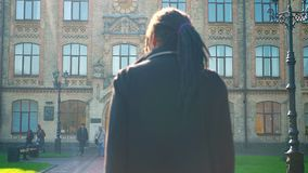 Rear-view of young African-American student with dreadlocks going to university in sunshine. Rear-view of young African-American student with dreadlocks going stock footage