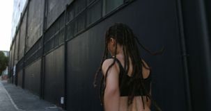 Rear view of young African American woman jogging in the city 4k stock video footage