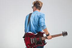 Rear view of young artist holding a guitar in studio Stock Image