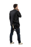 Rear view of young artist looking at blank white wall. Stock Photo