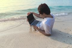 Rear view of young Asian man with laptop lying down on the sandy of beach. stock photo
