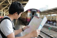 Rear view of young Asian tourist with a bag looking at map in train station with copy space background. Rear view of young Asian tourist with a bag looking at Royalty Free Stock Photo