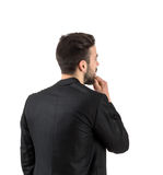 Rear view of young bearded guy looking at white wall Stock Photo