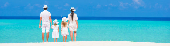 Rear view of young beautiful family on white stock photography