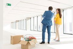 Rear view of young business people discussing by cardboard boxes in new office Stock Photos