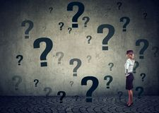 Businesswoman with hand on head standing in front of a wall with many questions stock photo