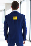 Rear view of young businessman with hire me adhesive note at office Stock Image