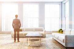 White couches in white living room, businessman stock photography