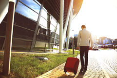 Rear view of young Businessman walking down street with luggage. Rear view of young Businessman walking down the street with luggage Stock Images