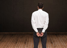 Rear view of young businessman wearing handcuffs Stock Image