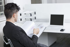 Rear view of young businessman working at office Stock Image
