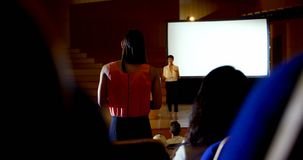 Young businesswoman asking questions to Asian female speaker during seminar in auditorium 4k. Rear view of young businesswoman asking questions to Asian female stock video footage