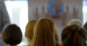 Businesswoman raising her hand up in the business seminar 4k. Rear view of a young businesswoman sitting and raising her hand up to ask a question in the stock video footage