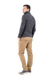 Rear view of young casual man in gray sweater looking up over shoulder Royalty Free Stock Images