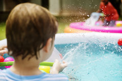 Rear view of young caucasian boy in inflatable pool Stock Photo