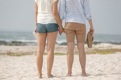 Caucasian couple standing at beach with footwear in hand royalty free stock images