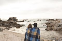 Caucasian couple wrapped in blanket standing at  beach royalty free stock images
