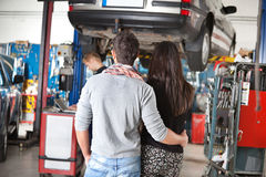 Rear view of young couple in garage Stock Photos