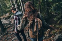 Best way to escape from the city. Rear view of young couple hiking together in the woods while enjoying their travel Stock Images