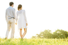 Rear view of young couple holding hands in park against clear sky Royalty Free Stock Photo