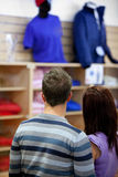 Rear view of a young couple looking at men clothes Stock Photos