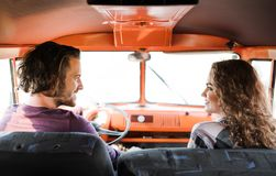 A rear view of young couple on a roadtrip through countryside, driving minivan. A rear view of young couple on a roadtrip through countryside, driving retro stock image