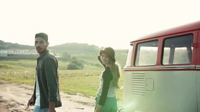 A rear view of young couple on a roadtrip through countryside, walking. stock video footage
