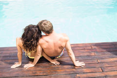 Rear view of young couple sitting by poolside Stock Photos
