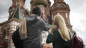 Young tourists couple taking pictures of Moscow cathedral near Kremlin, Russia. Rear view of a young couple taking pictures of Moscow Saint Basil`s Cathedral stock video footage