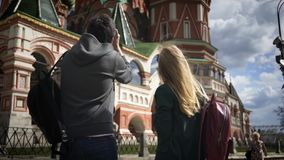 Young tourists couple taking pictures of Moscow near Kremlin, Russia. Rear view of a young couple taking pictures of Moscow Saint Basil`s Cathedral, Russia stock video footage