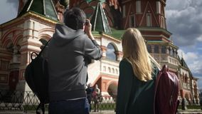 Rear view of young couple tourists taking pictures of Moscow cathedral, Kremlin. Rear view of a young couple taking pictures of Moscow Saint Basil`s Cathedral stock video footage
