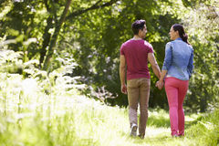 Rear View Of Young Couple Walking In Summer Countryside Stock Photography