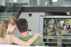 Rear view of young couple watching television in living room Stock Photo