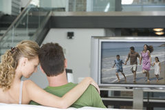 Rear view of young couple watching television in living room Stock Photos