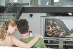 Rear view of young couple watching television in living room Royalty Free Stock Images