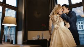 Rear view of the young elegant couple of newlyweds tenderly hugging and kissing in luxury restaurant. stock video