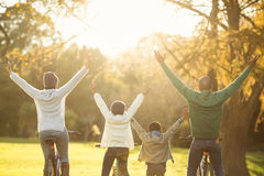 Rear view of a young family with arms raised on bike Stock Photo