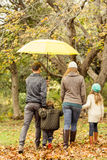 Rear view of young family under umbrella Royalty Free Stock Images