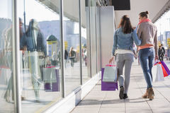 Rear view of young female friends with shopping bags walking on sidewalk Stock Photography