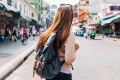 Young female tourist backpacker on Khao San road in Bangkok, Thailand. Rear view of young female tourist backpacker walking on Khao San road in summer during stock photos