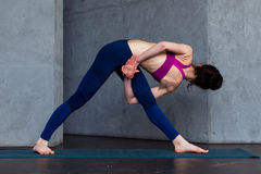 Rear view of young female yogi in sports bra and leggings doing bound extended side angle pose, baddha utthita. Parsvakonasana, while practicing yoga indoors Stock Photography
